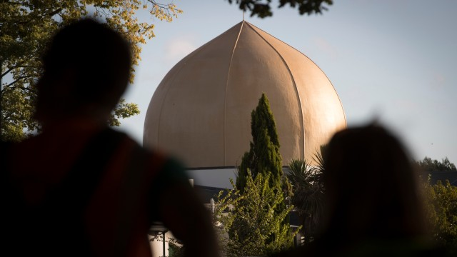 Mourners stand in front of the Masjid Al Noor mosque in Christchurch.