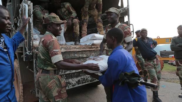 Soldiers hand out food supplies in Zimbabwe (Tsvangirayi Mukwazhi/AP)
