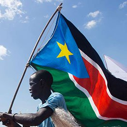 A man carries the South Sudan flag at Magateen Internal Displaced