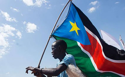 A man carries the South Sudan flag at Magateen