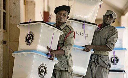 Security workers carry ballot boxes at a