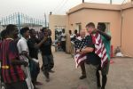 Djiboutian Doudou Roblah drapes a flag over U.S. Army Capt. Noah Hodges' shoulders as Capt. Mike Volk and Roblah's friends look on outside a vocational school in the capital of Djibouti on Thursday, June 13, 2019. U.S. Embassy officials say an English language discussion group the soldiers lead at the school helps to support diplomatic and development efforts in Africa.<br>Chad Garland/Stars and Stripes