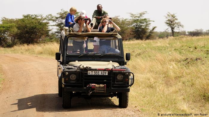 An open-topped Land Rover with tourists in the Serengeti National Park (picture-alliance/dpa/F. von Poser)