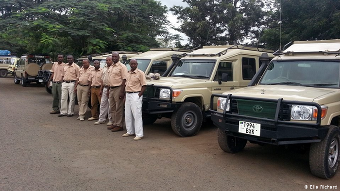 Tour guides wait for clients in Tanzania in front of safari vehicles